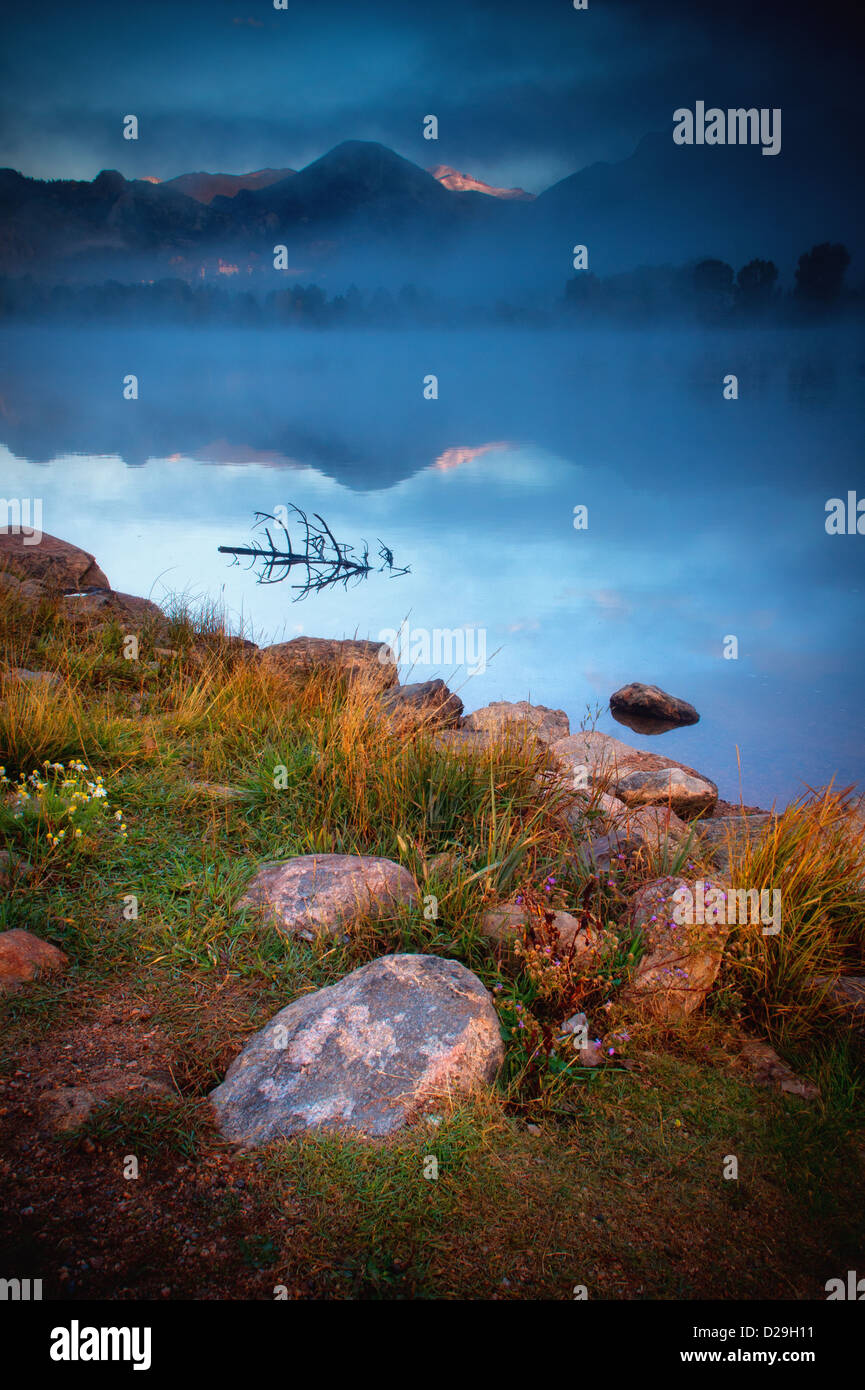 Fog begins to roll in over Lake Estes creating a dramatic scene at sunrise on a gorgeous Fall morning in Estes Park, - Stock Image