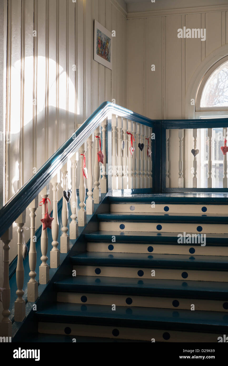 Painted stair with decorations on turned white handles - Stock Image