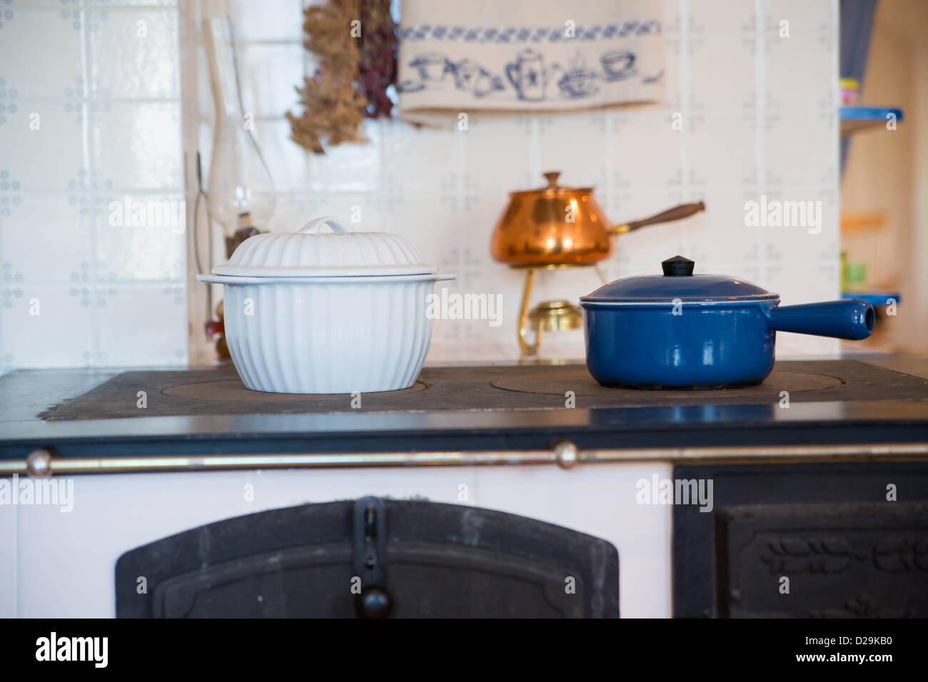 Different shape saucepans with soups warming on stove - Stock Image