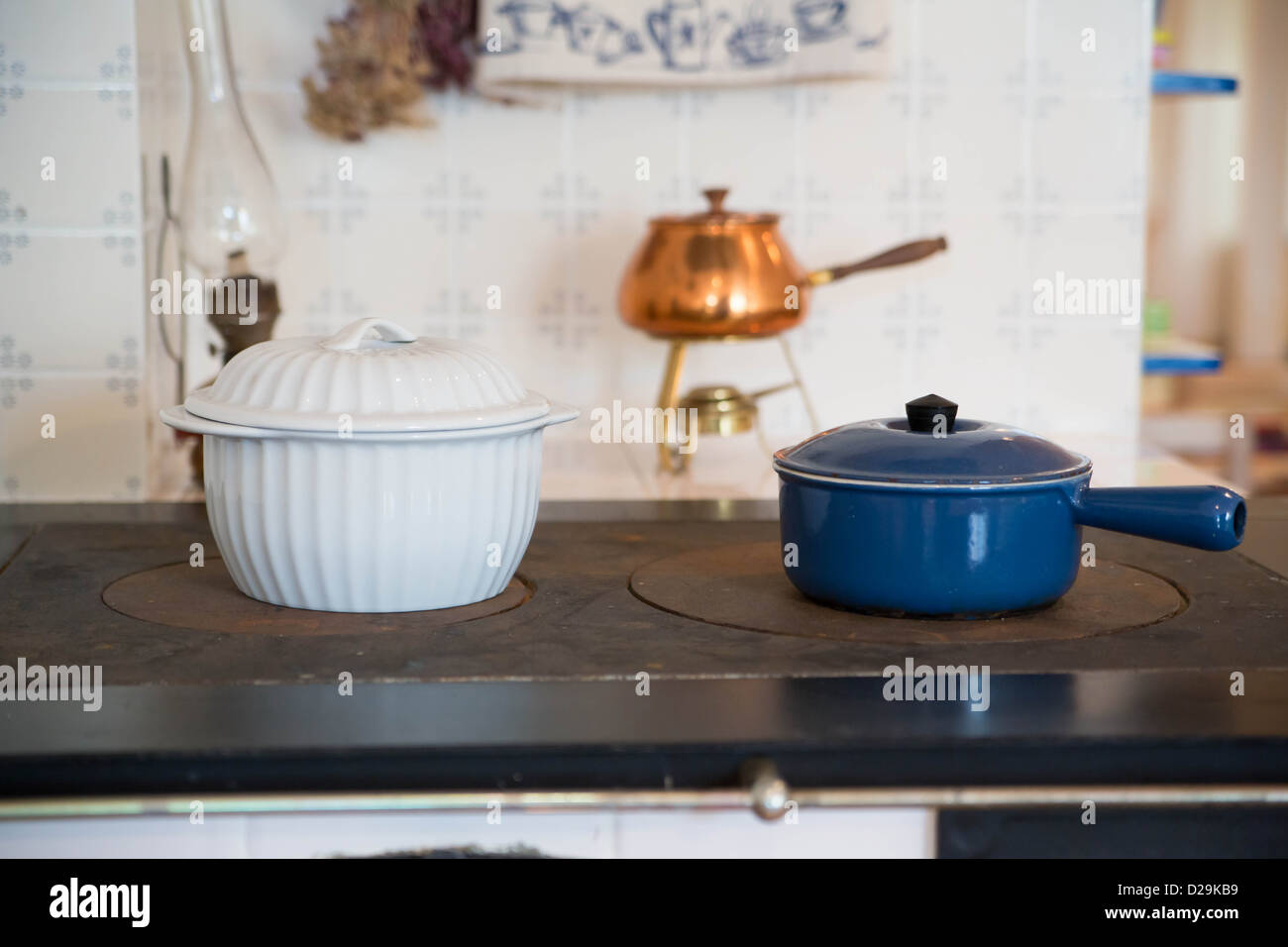 Zoomed shape saucepans with soups warming on stove - Stock Image