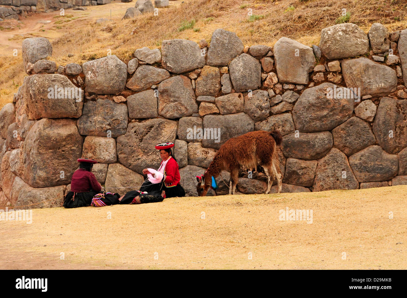 Peru, Women Weaving By Stone Wall - Stock Image