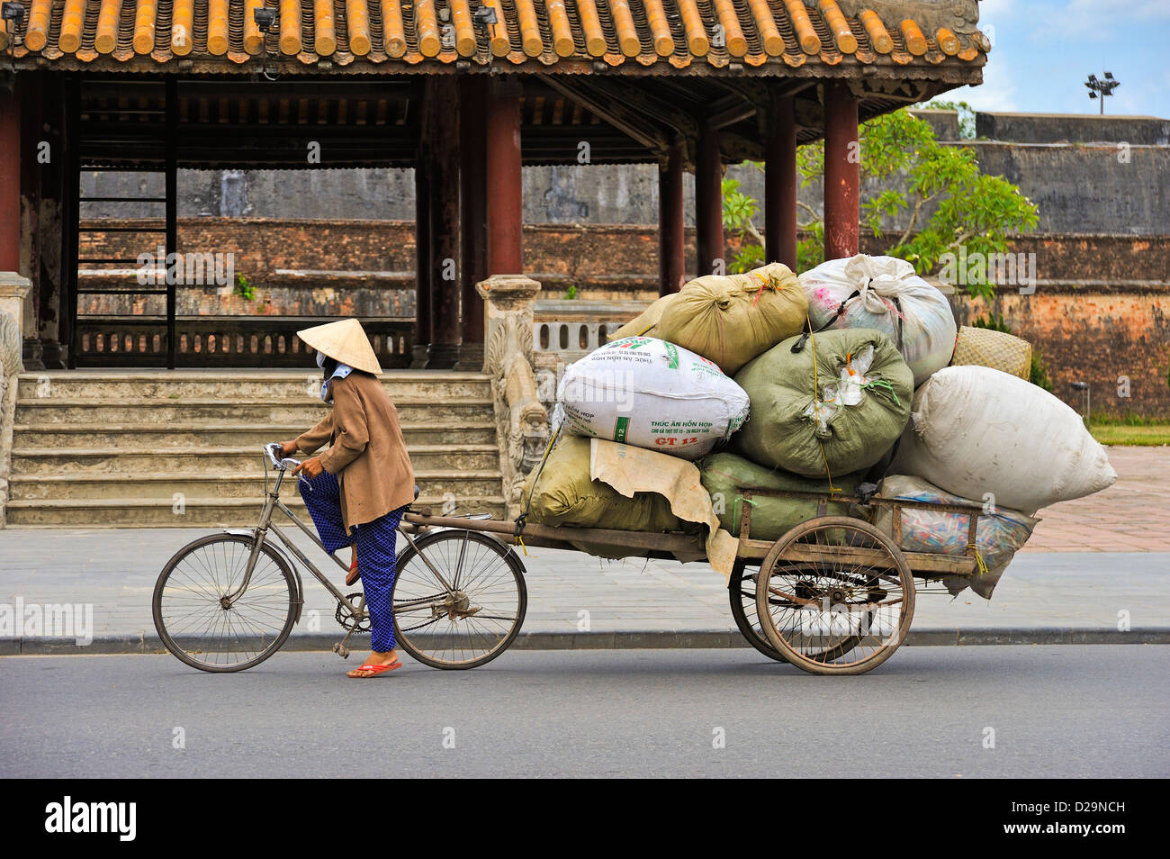 Vietnam, Hue - Woman pulling a very large load on a bicycle - people street scene - Stock Image