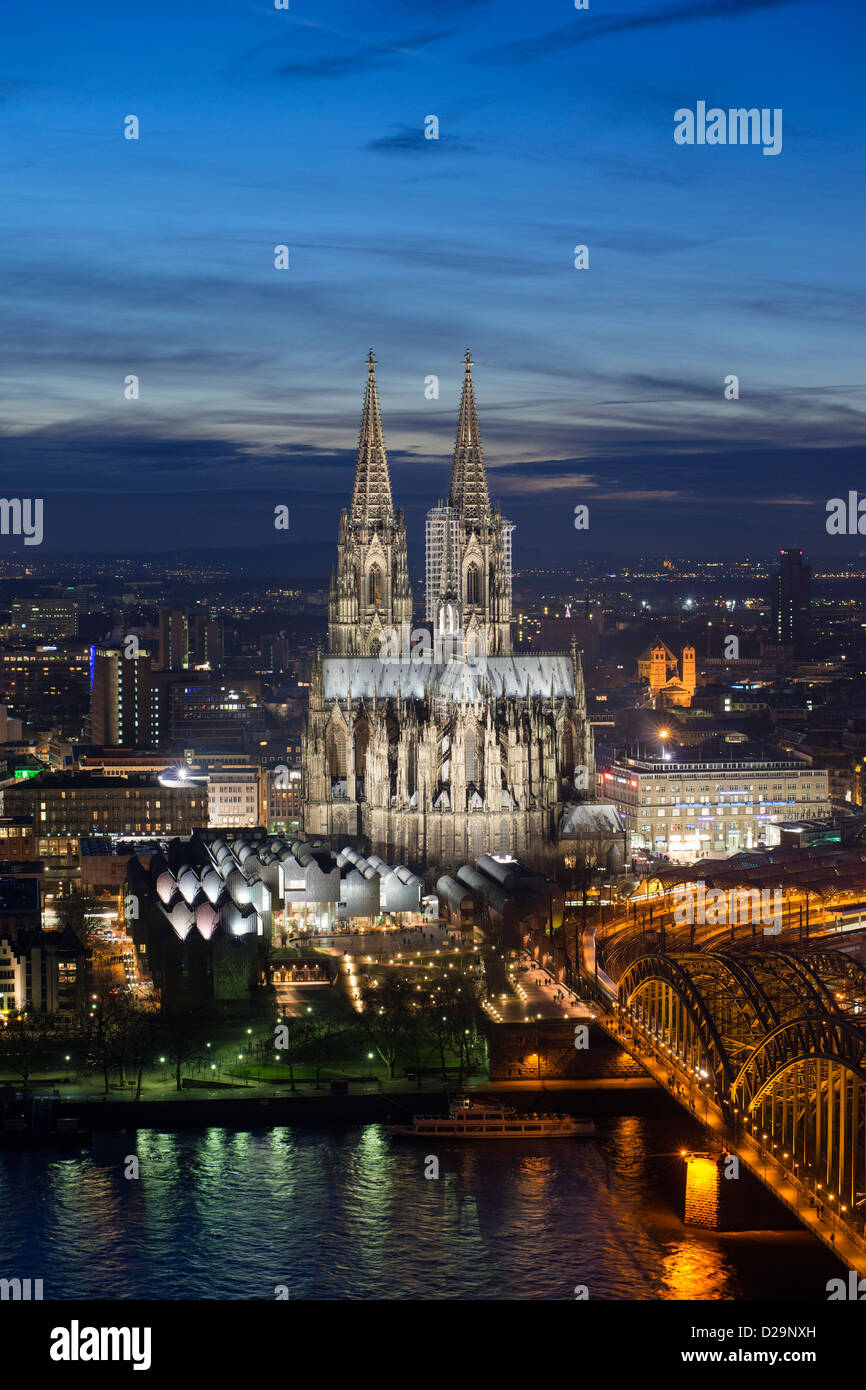 Evening view of skyline of Cologne, Germany with floodlit Cathedral prominent - Stock Image