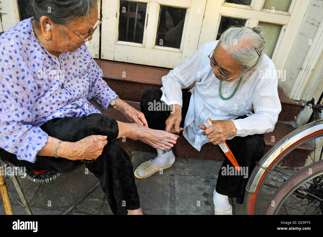 Woman having her feet treated by another old woman, Hanoi, Vietnam - Stock Image