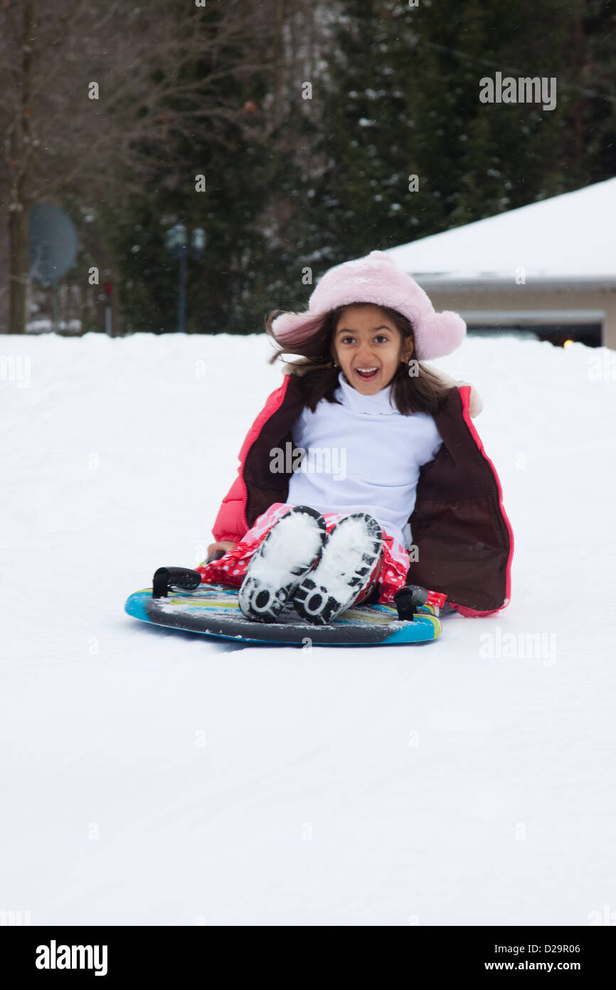 A happy East Indian girl goes down a slope on a toboggan Stock Photo