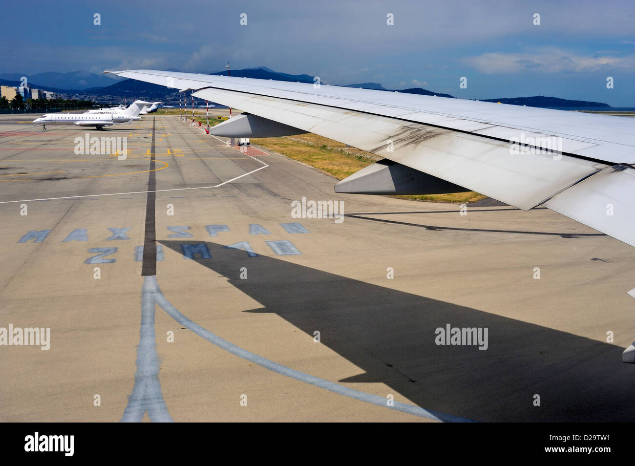 Airplane wing taxiing at an International airport, France - Stock Image