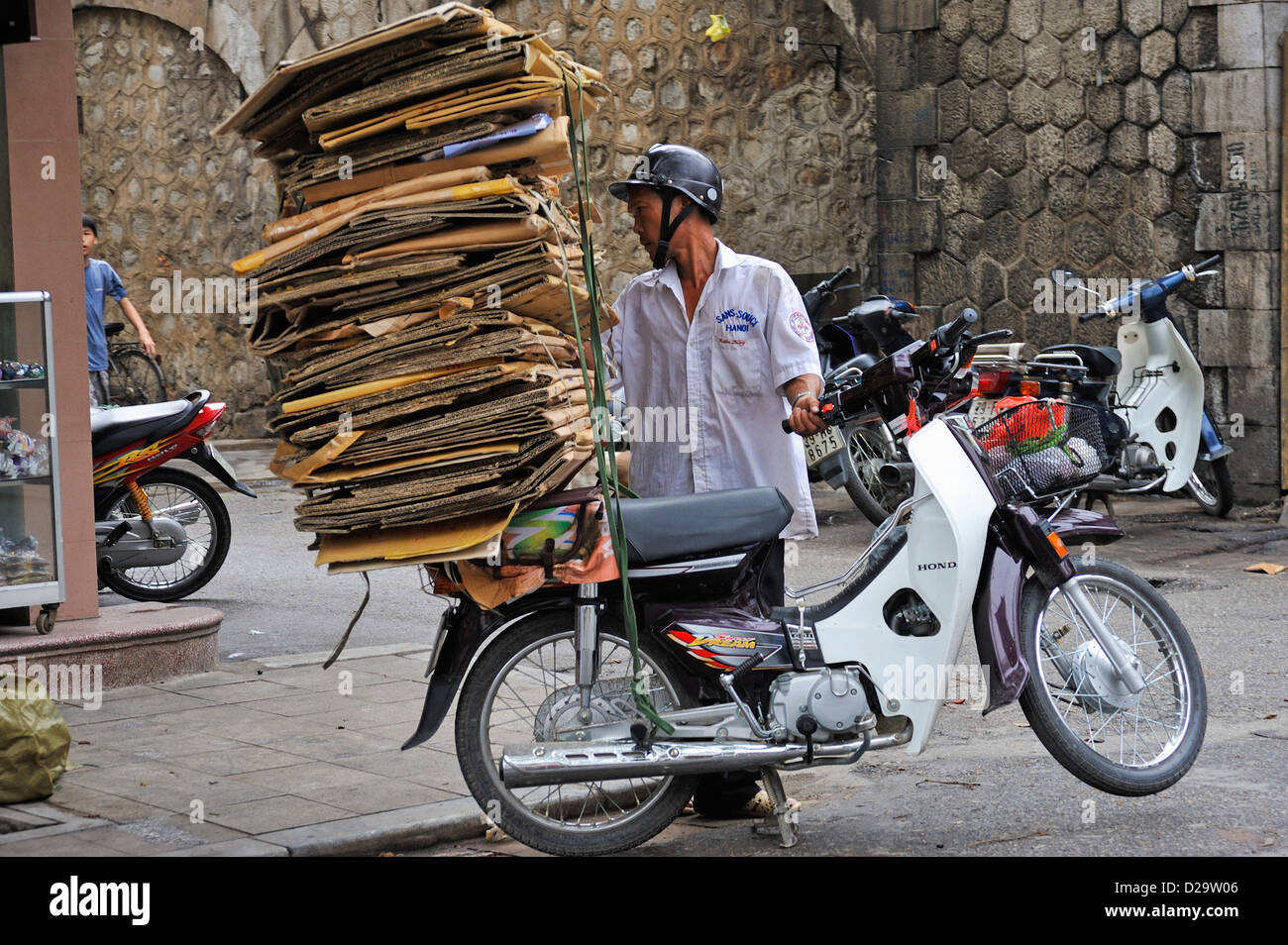 Man carrying cardboard on the back of his scooter, Hanoi, Vietnam - Stock Image