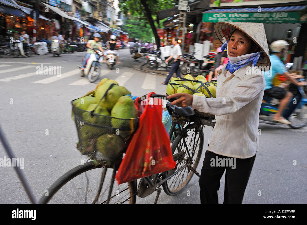 Hanoi, Vietnam - Woman selling / carrying fruit - people in Vietnam street scene - Stock Image