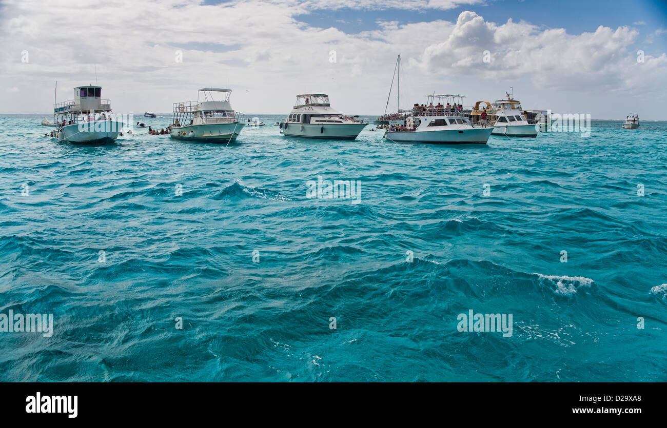 Group of Tour boats floating in turquoise water at the sandbar at Stingray City in Grand Cayman - Stock Image