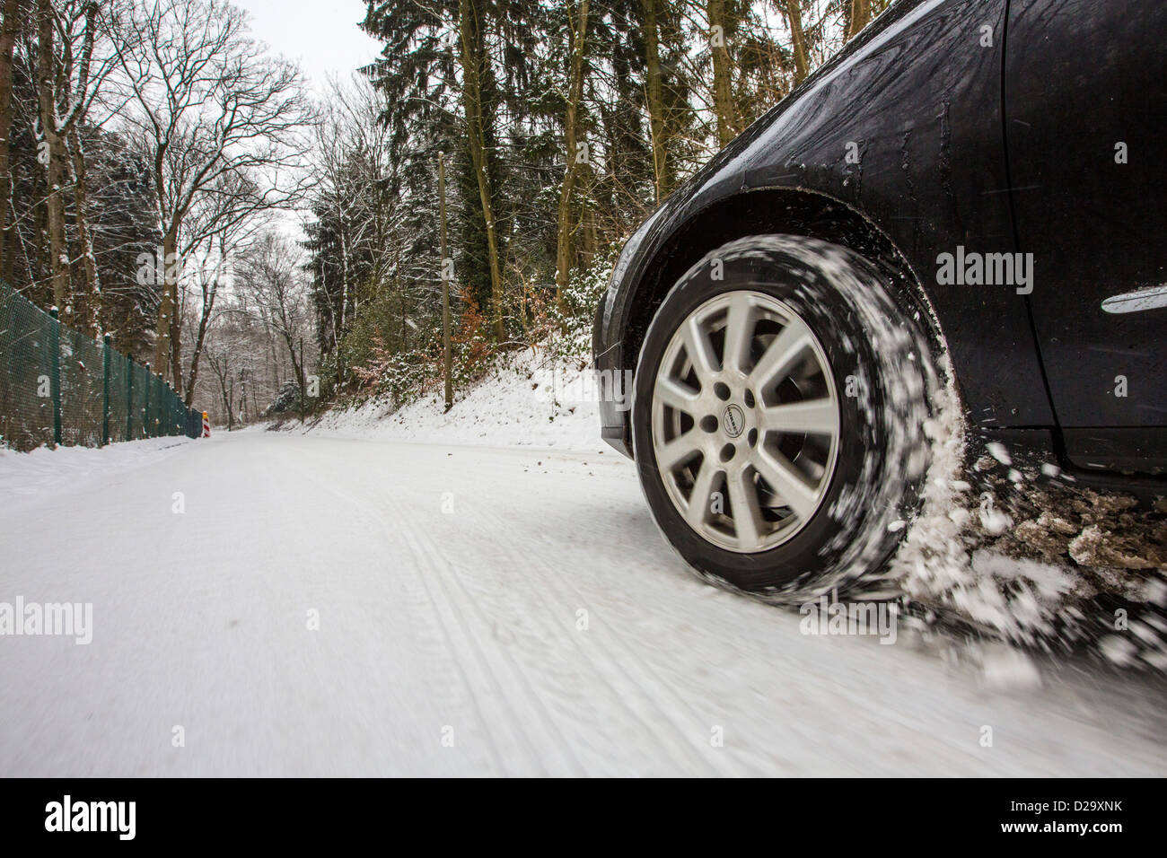 Car with winter tires drives on a street, completely covered with snow. - Stock Image