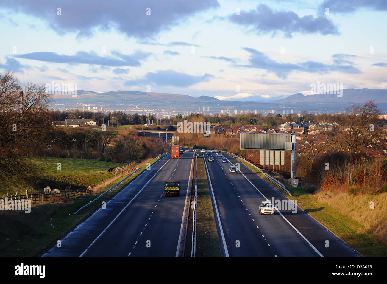 The M77 motorway entering the city of Glasgow and beyond to the Campsies on a sunny winter day whilst most of Britain - Stock Image