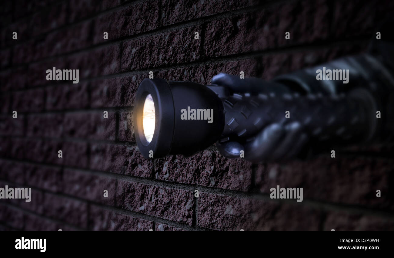 gloved hand holding a lit flashlight in the dark beside a brick wall. Low key. - Stock Image