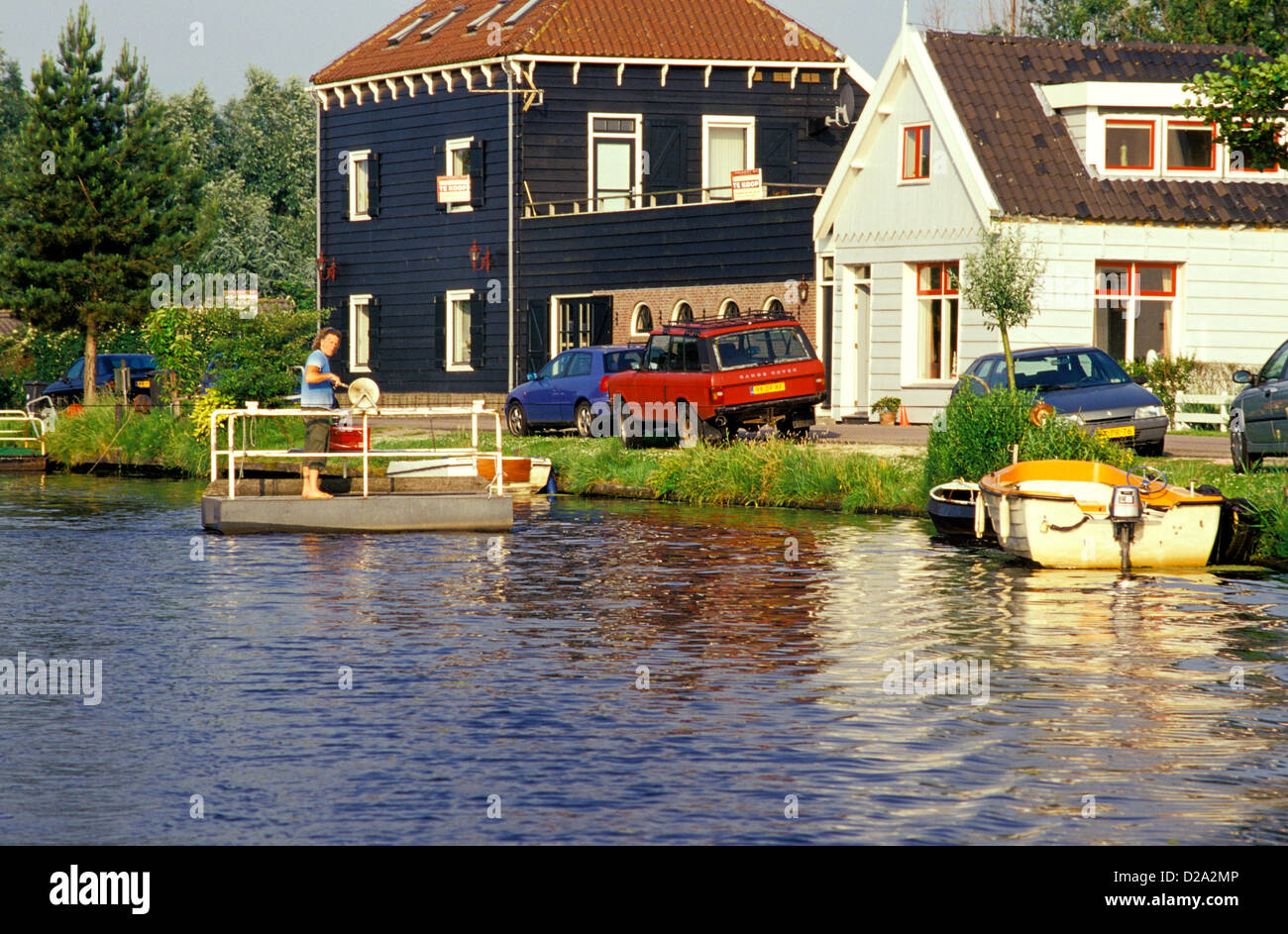 Netherlands. Near Amsterdam. Man Using Self-Powered Ferry To Cross Canal. - Stock Image