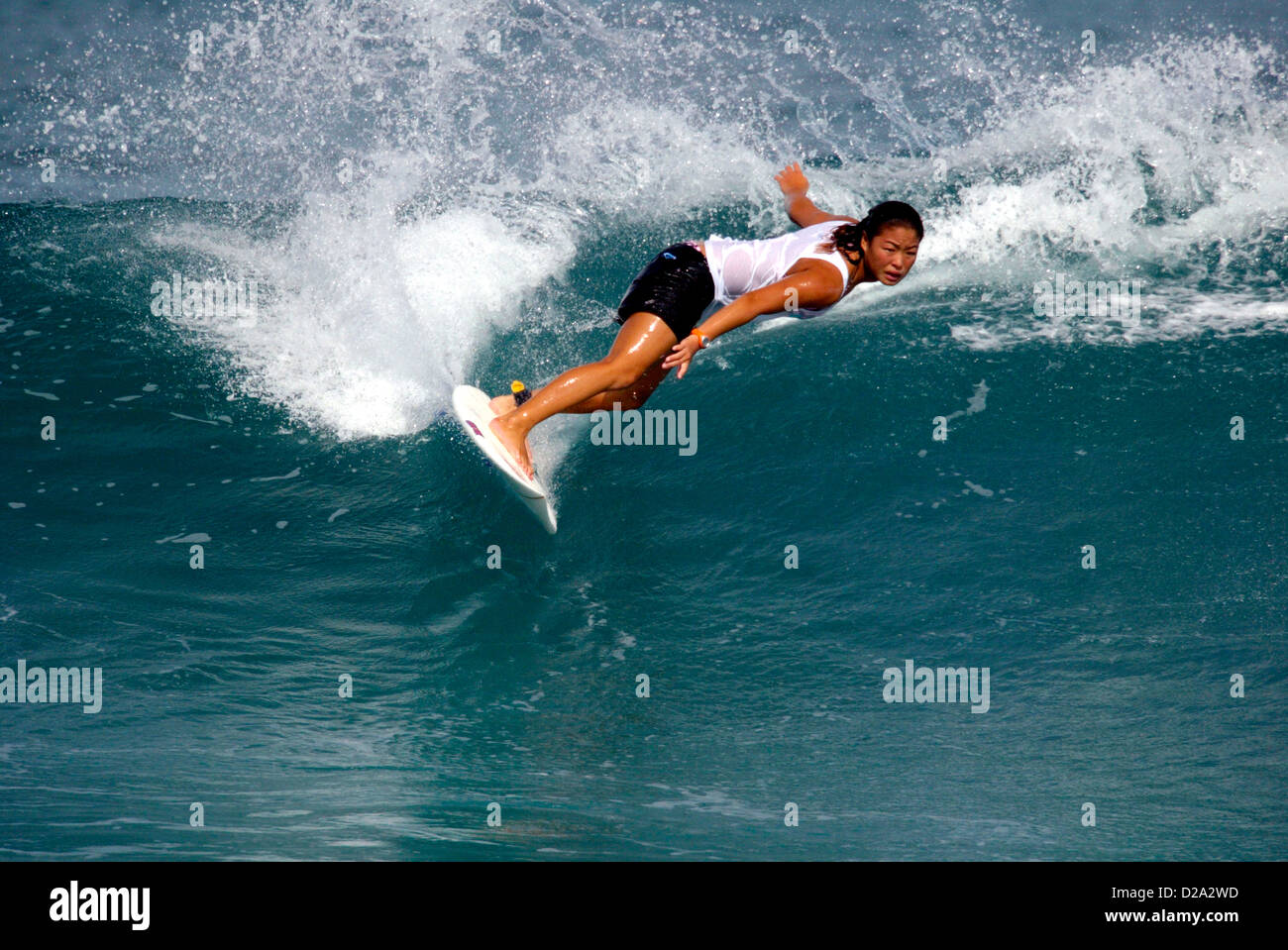 Hawaii, Oahu. Girl Surfing At 'Gas Chambers' - Stock Image