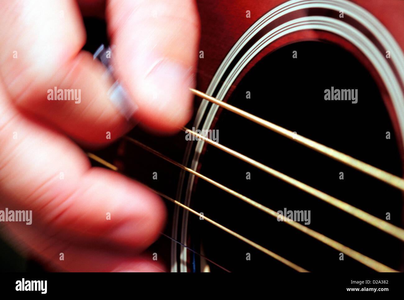 Close-Up Of Man'S Hand Strumming Guitar Strings - Stock Image