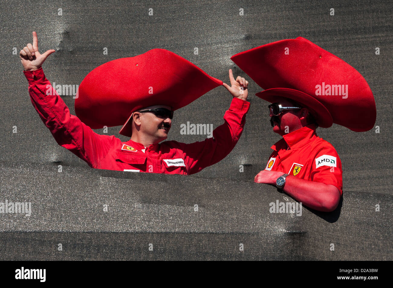 Two enthusiastic Texan fans of the Ferrari Formula 1 racing team sporting enormous, red cowboy hats and face paint. - Stock Image