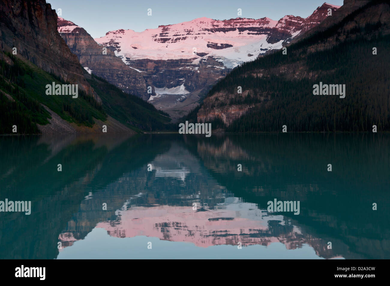 Morning alpenglow on Mount Victoria reflected in Lake Louise, Banff National Park, Canadian Rockies, Alberta, Canada. - Stock Image