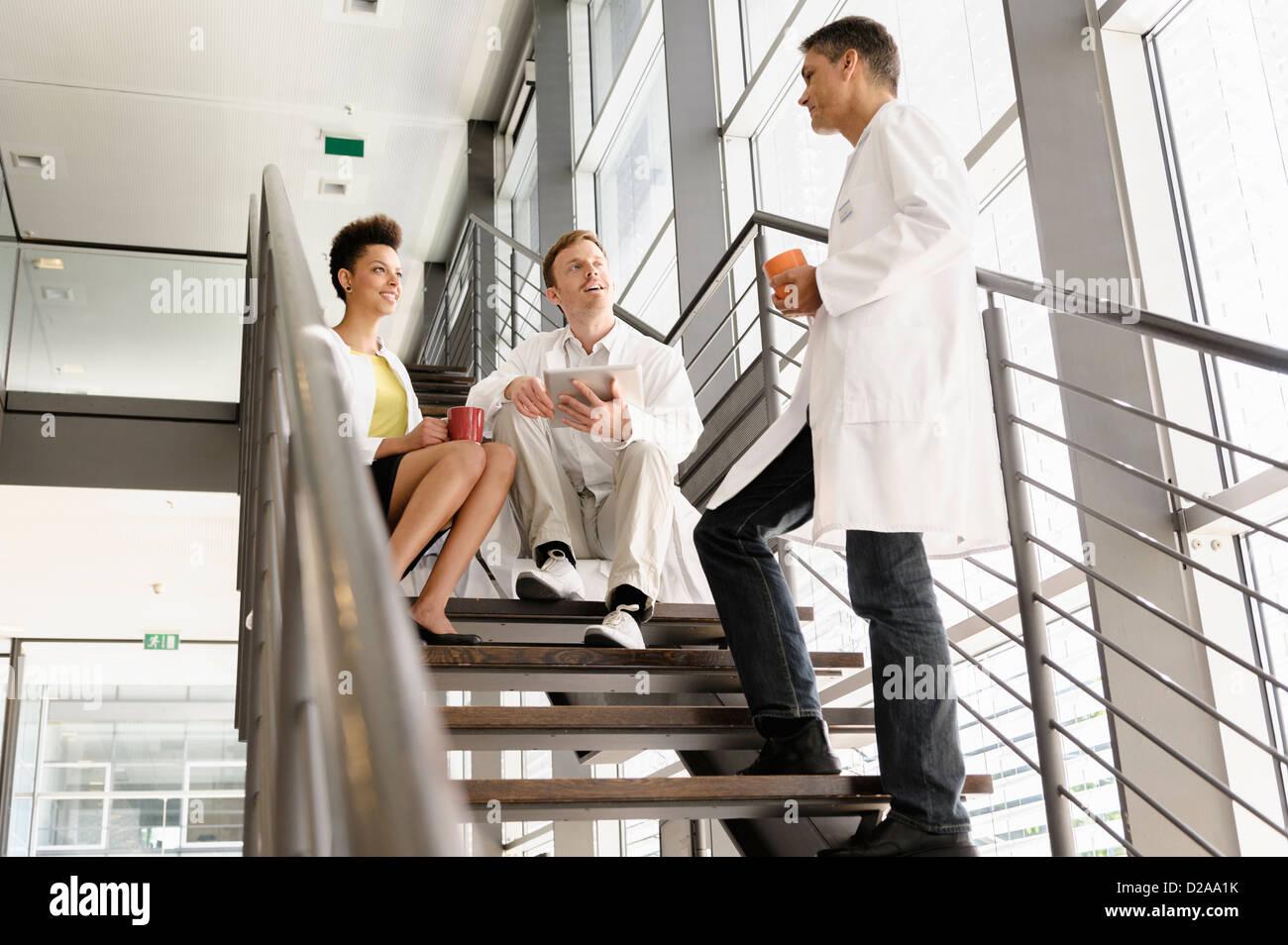 Doctors talking on steps in hospital - Stock Image