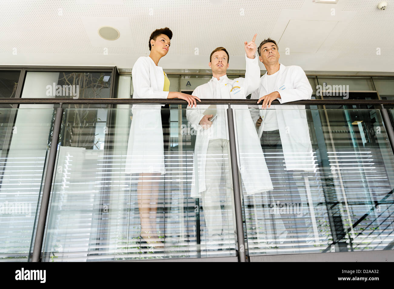 Doctors talking on balcony in hospital - Stock Image