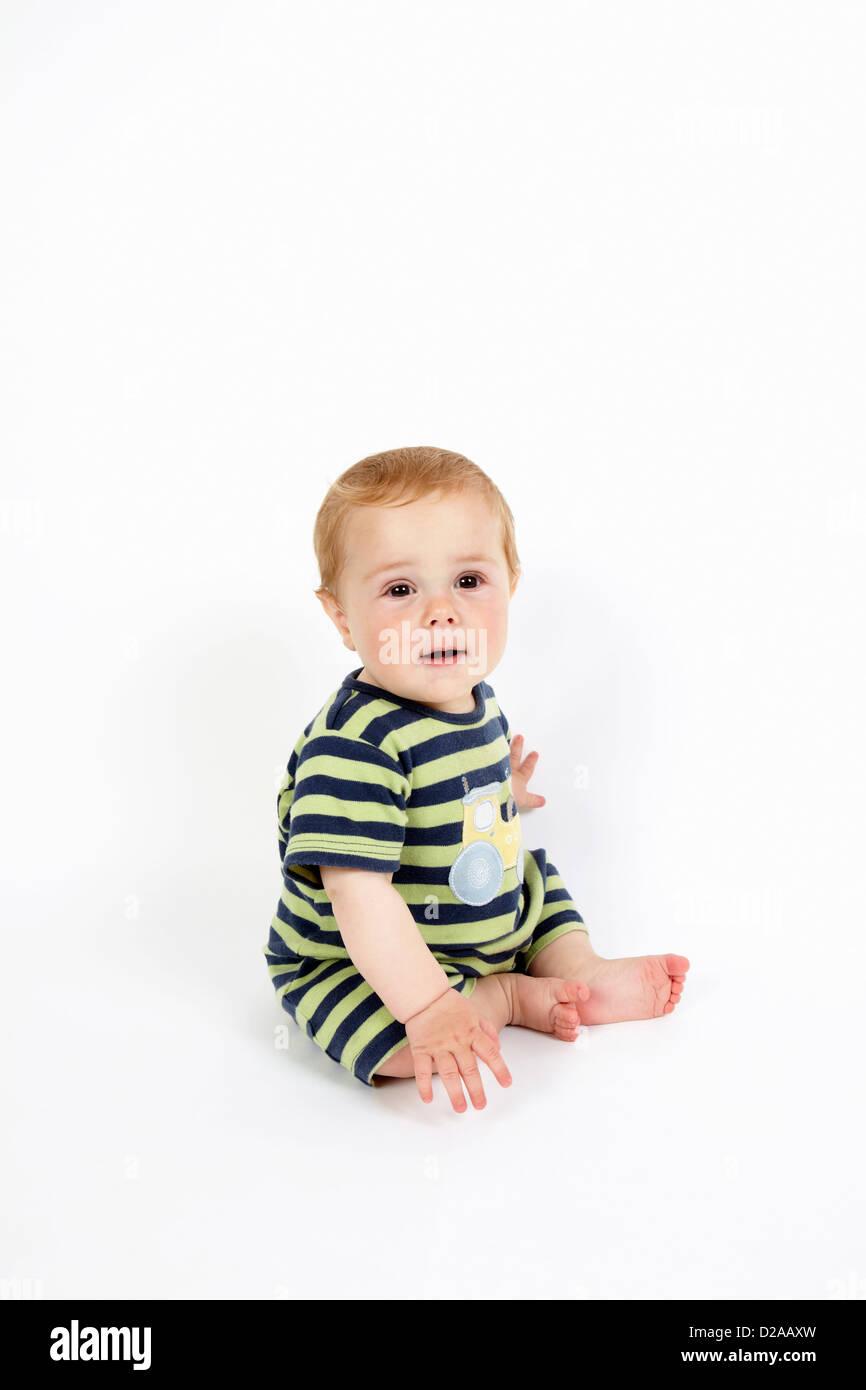 Toddler boy sitting on floor - Stock Image