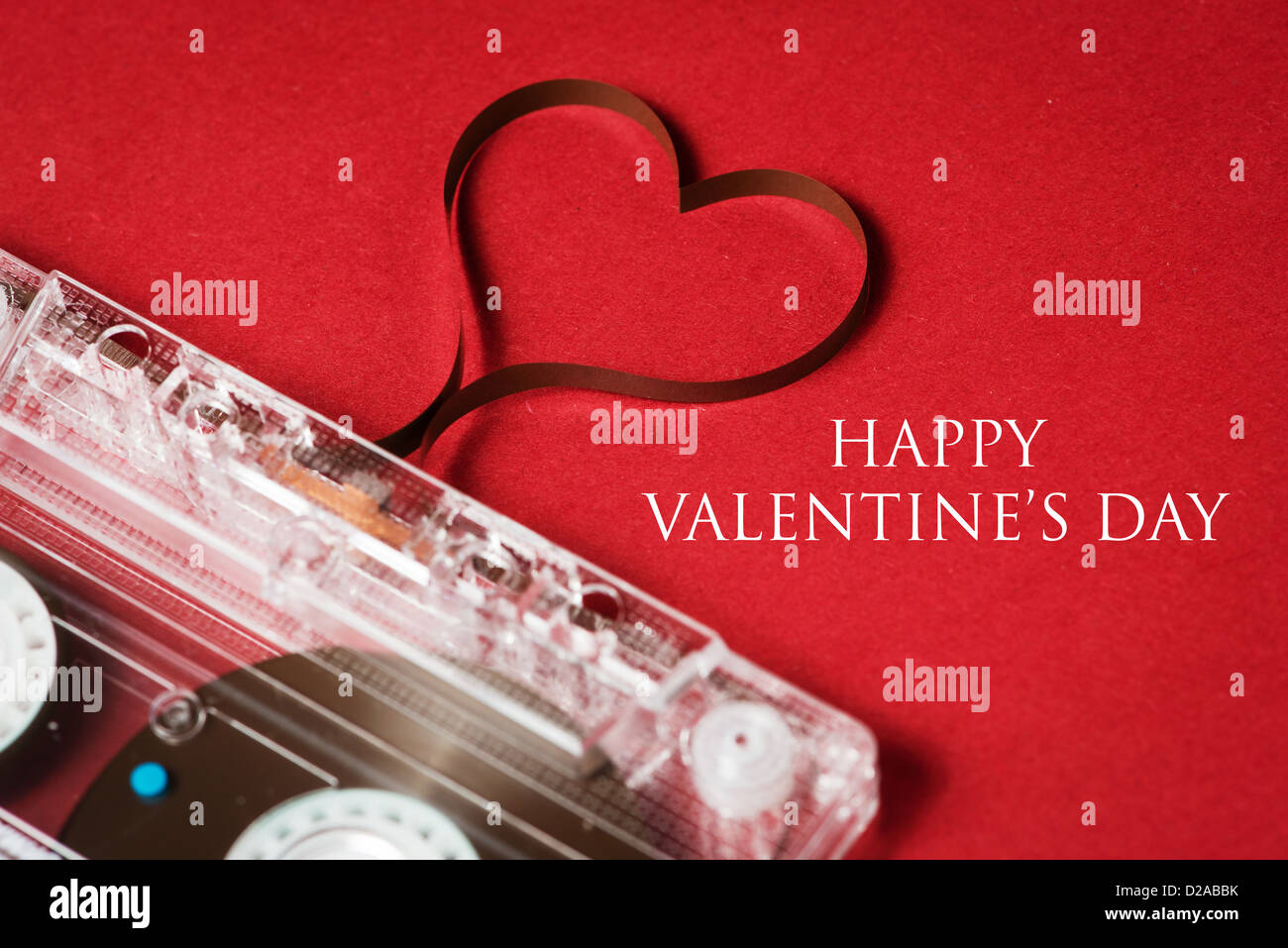 Valentines day card - audio cassette with magnetic tape in shape of heart on red background - Stock Image