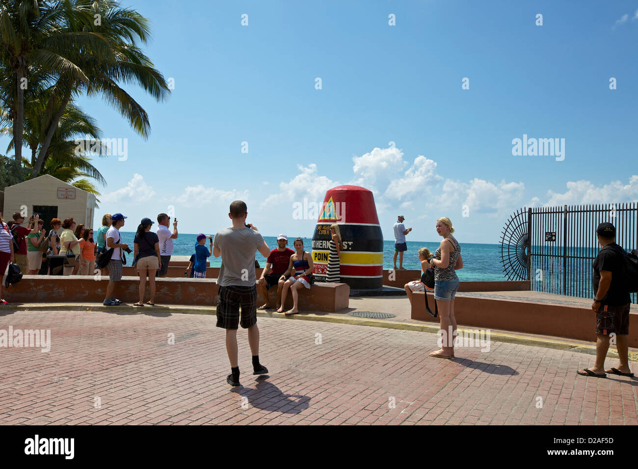 Tourists taking pictures at the Southernmost Point buoy in Key West - Stock Image