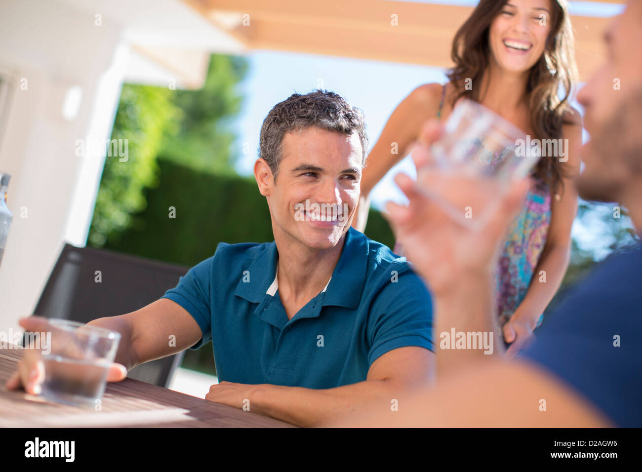 Men drinking water at table outdoors - Stock Image