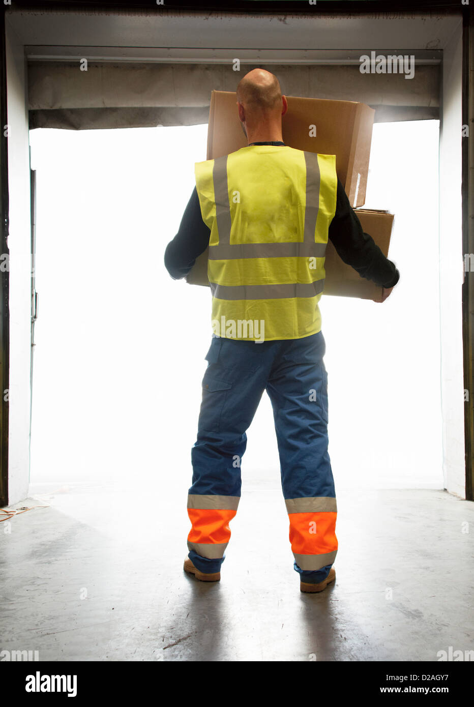 Worker carrying boxes in warehouse - Stock Image