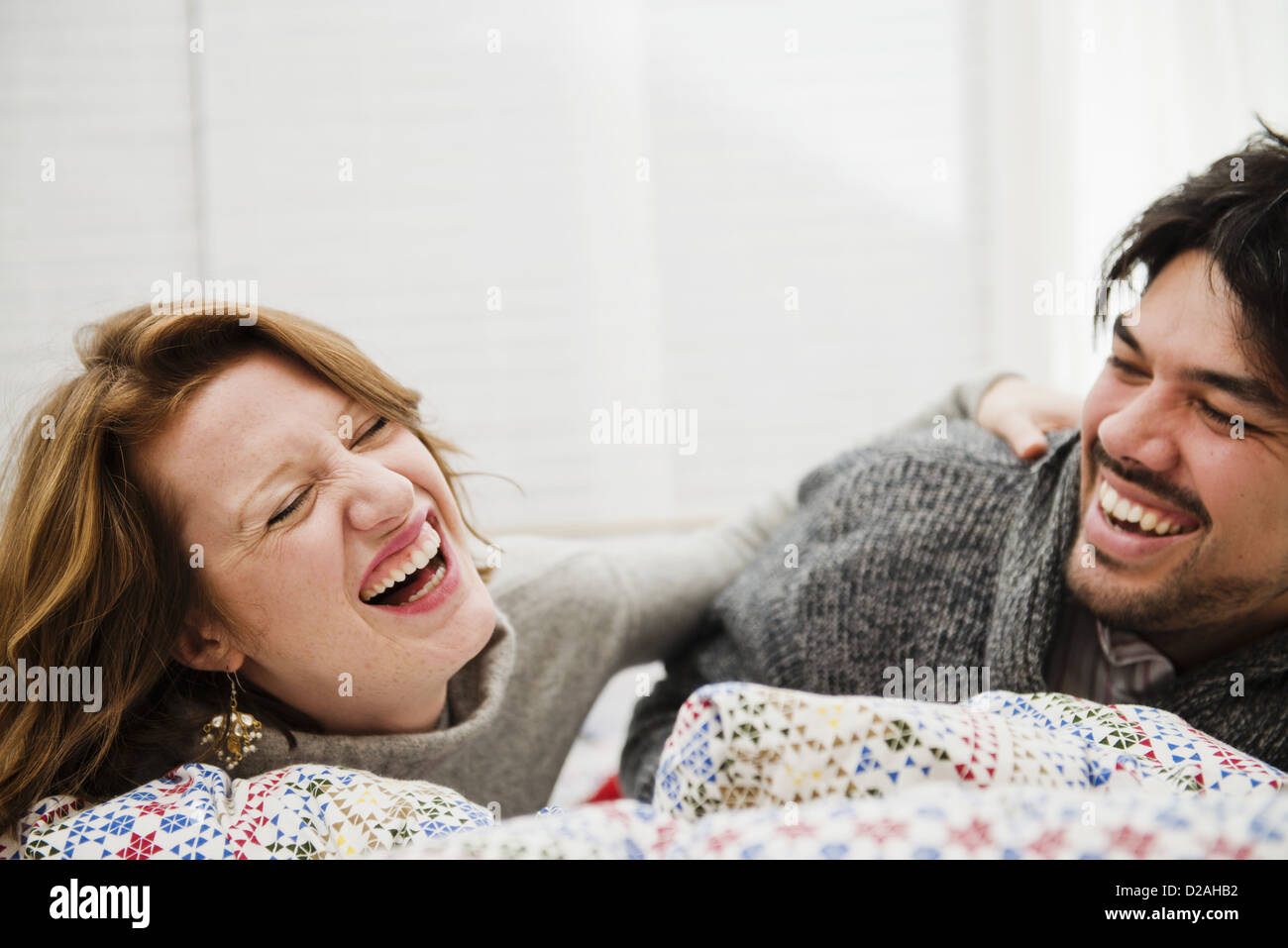 Couple laughing together on bed - Stock Image