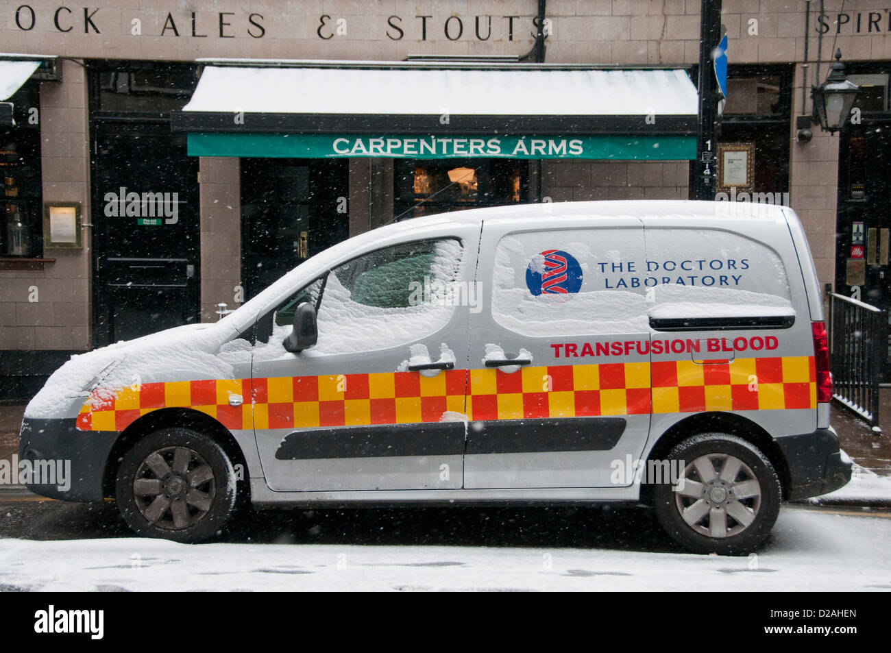London, UK. 18/01/13. A blood transfusion van is covered in a layer of snow, as snow falls in Central London. - Stock Image
