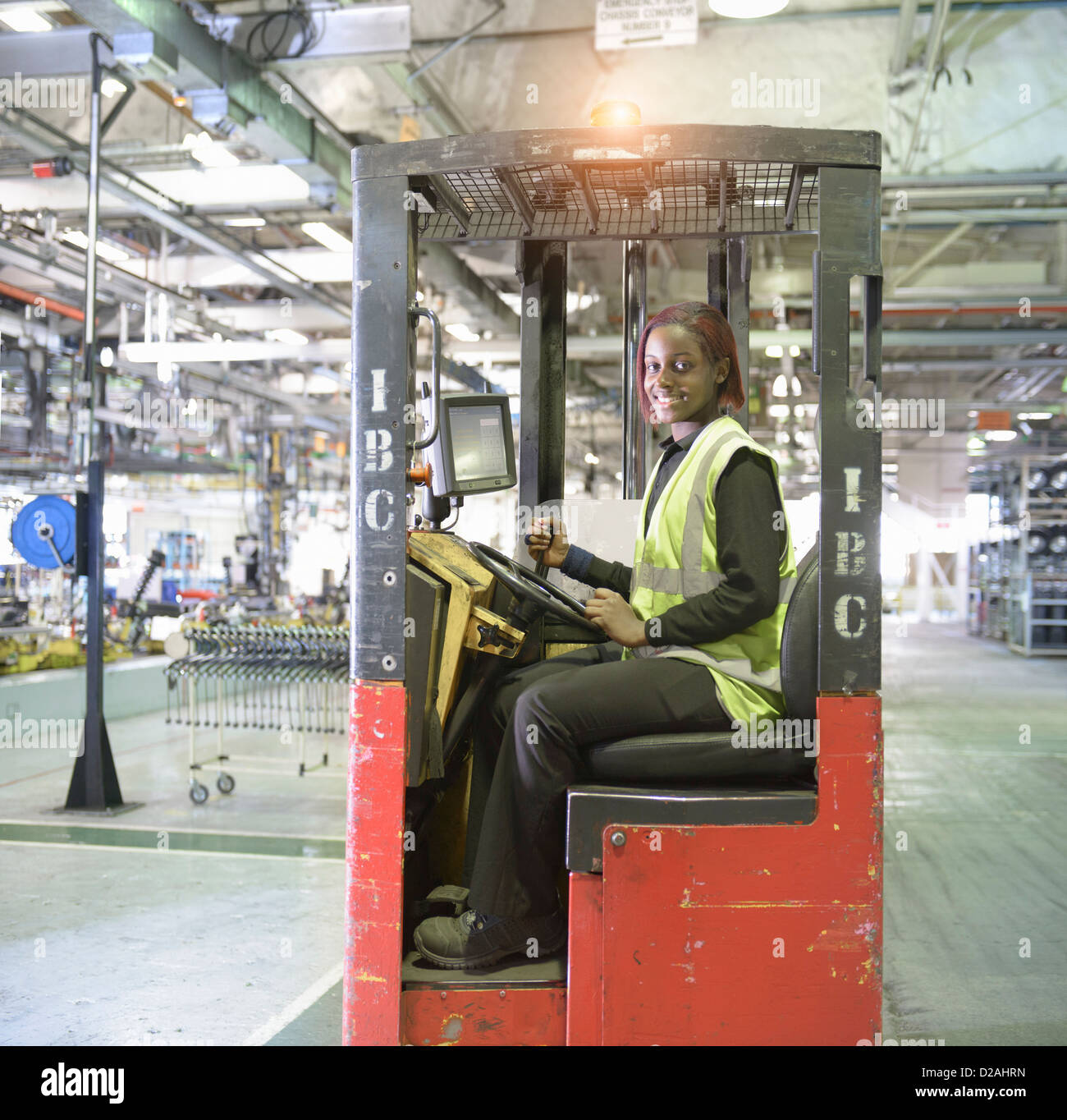 Apprentice lift operator in car factory Stock Photo