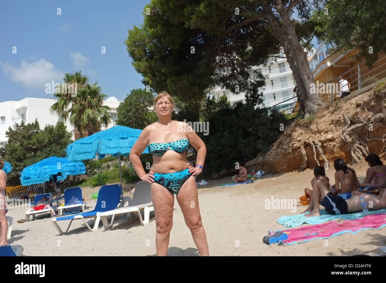 A middle-aged sunbather in Ibiza - Stock Image