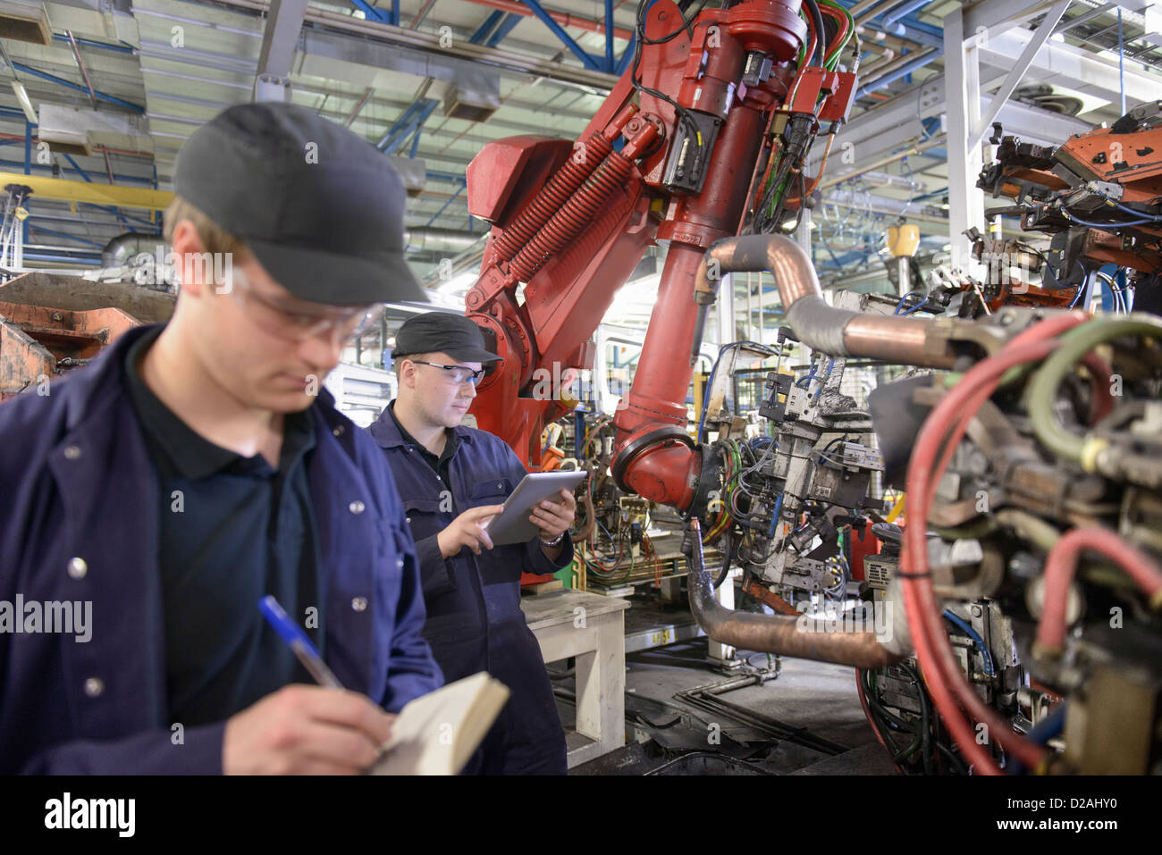 Apprentices with robots in car factory - Stock Image