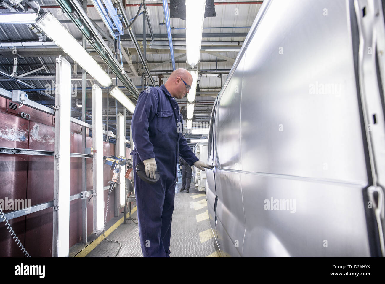 Worker inspecting vehicle in car factory - Stock Image