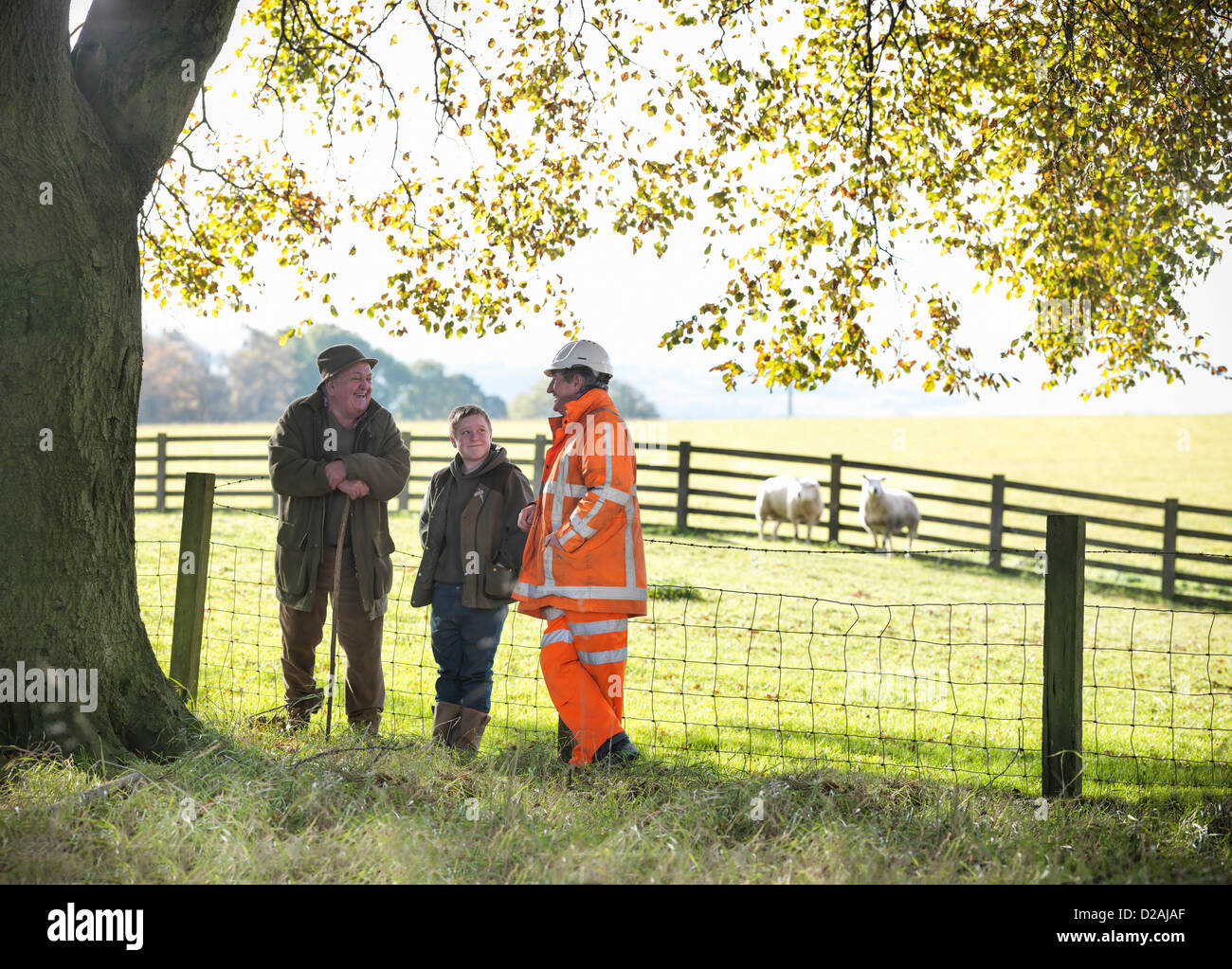 Ecologist and farmers talking in field - Stock Image