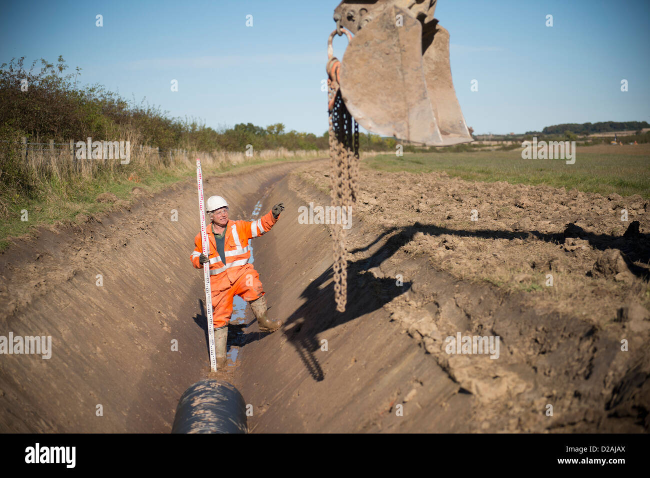 Worker directing digger in surface mine - Stock Image