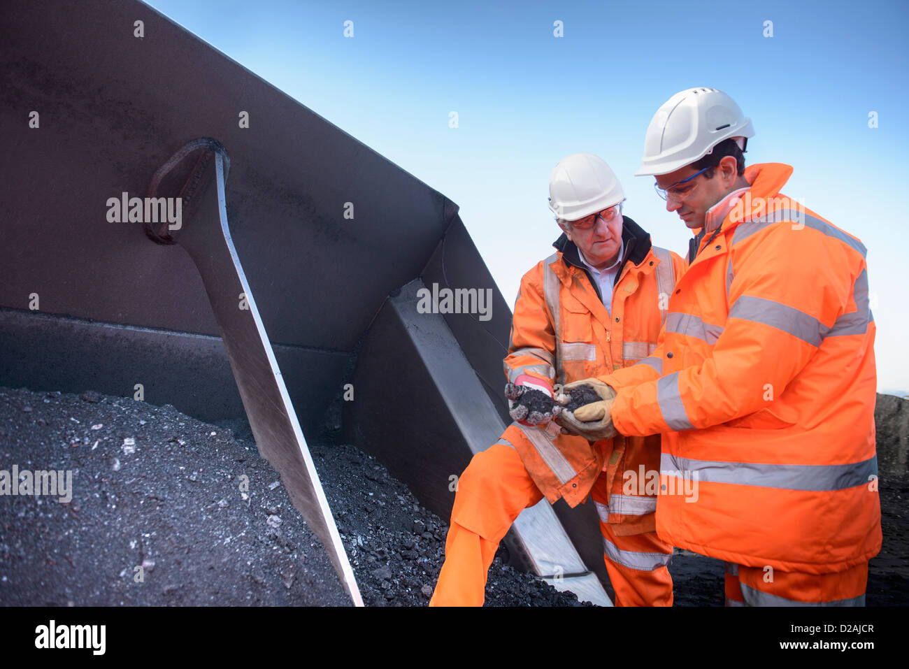 Workers inspecting coal at surface mine - Stock Image