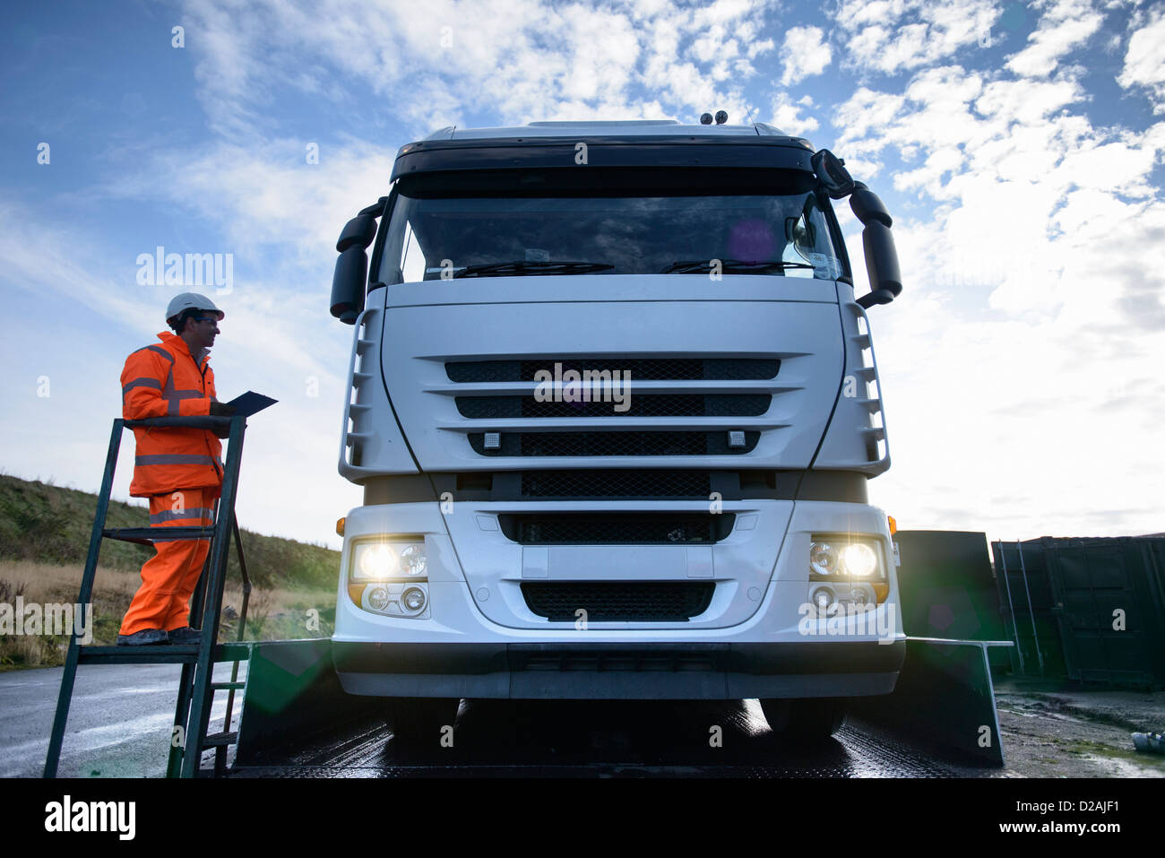 Worker directing truck on scales - Stock Image