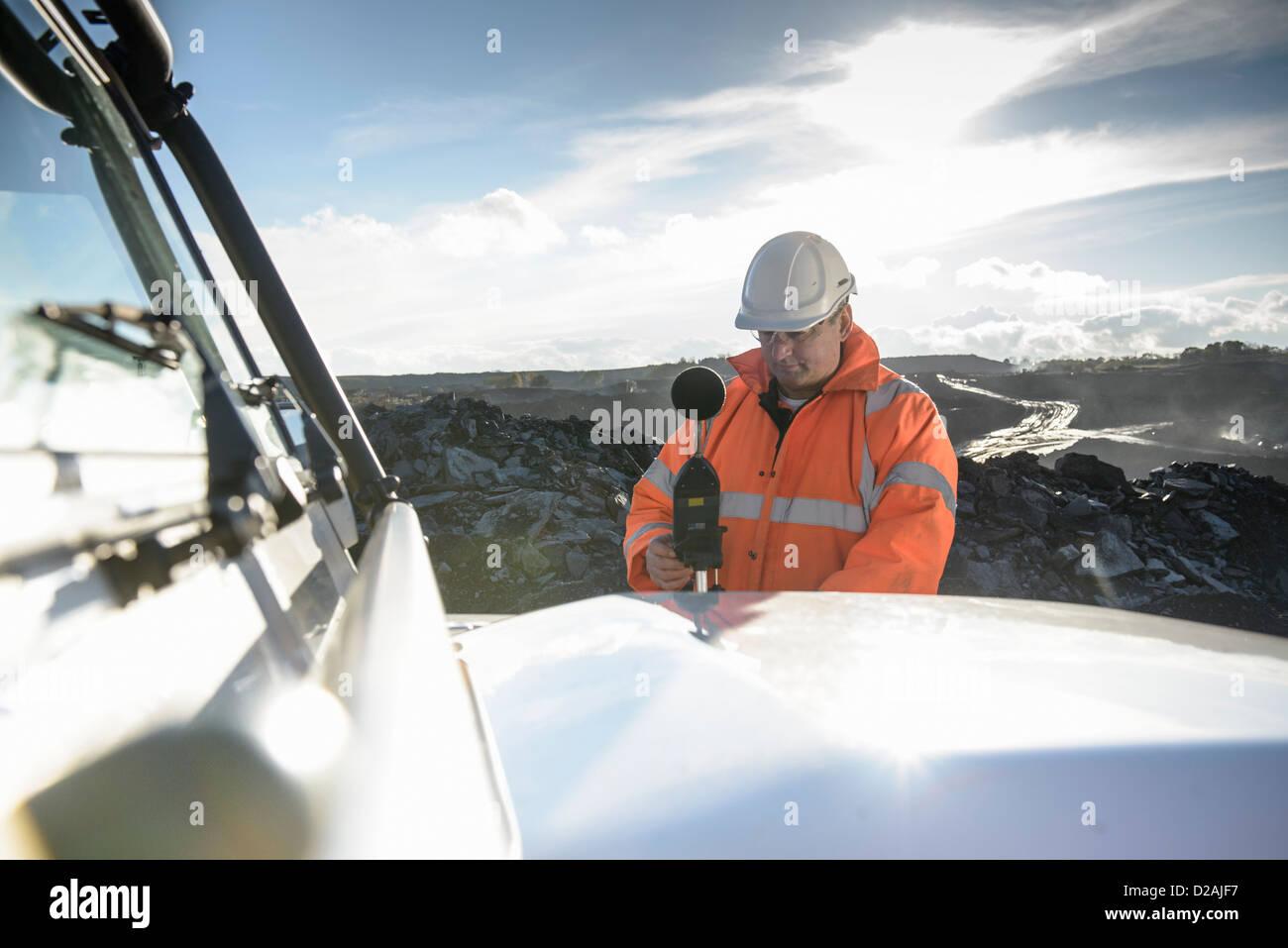 Worker using noise equipment on truck - Stock Image