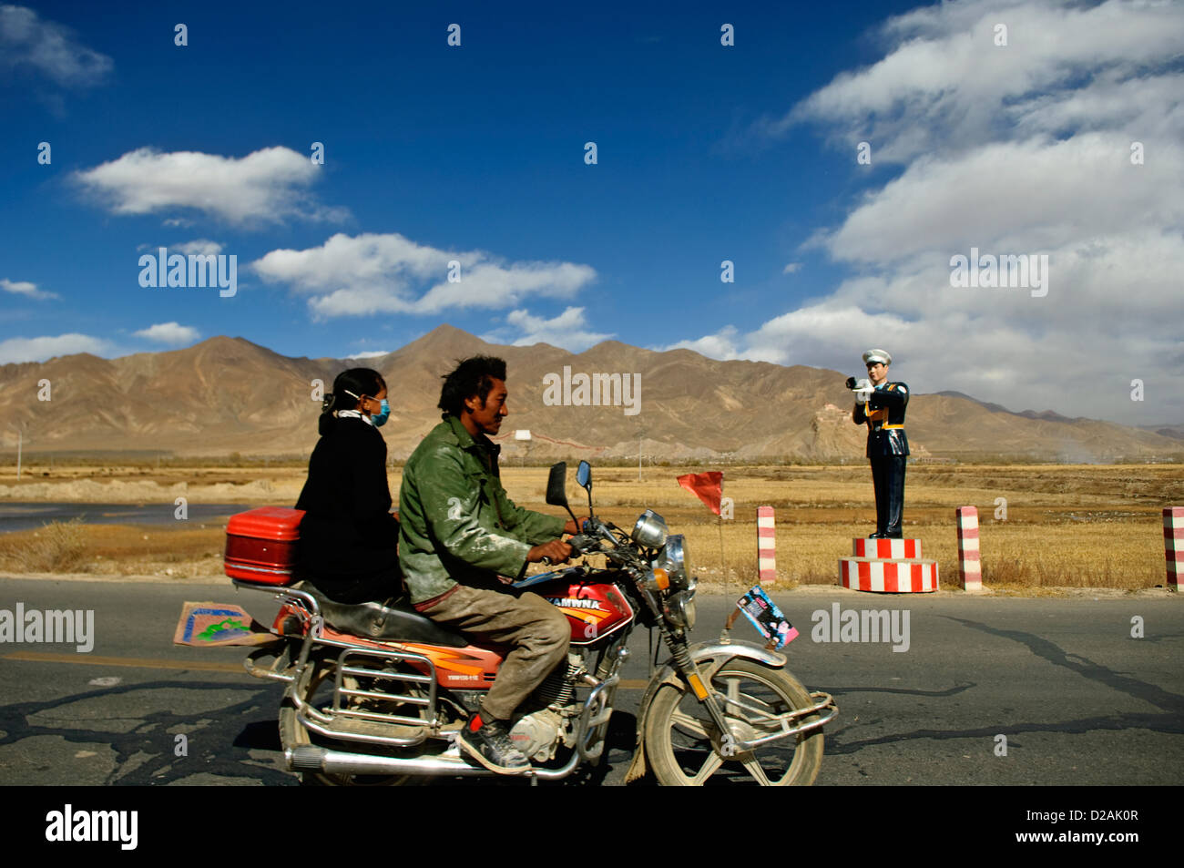 two people on a motorcycle passing by a fake policeman, tibet - Stock Image