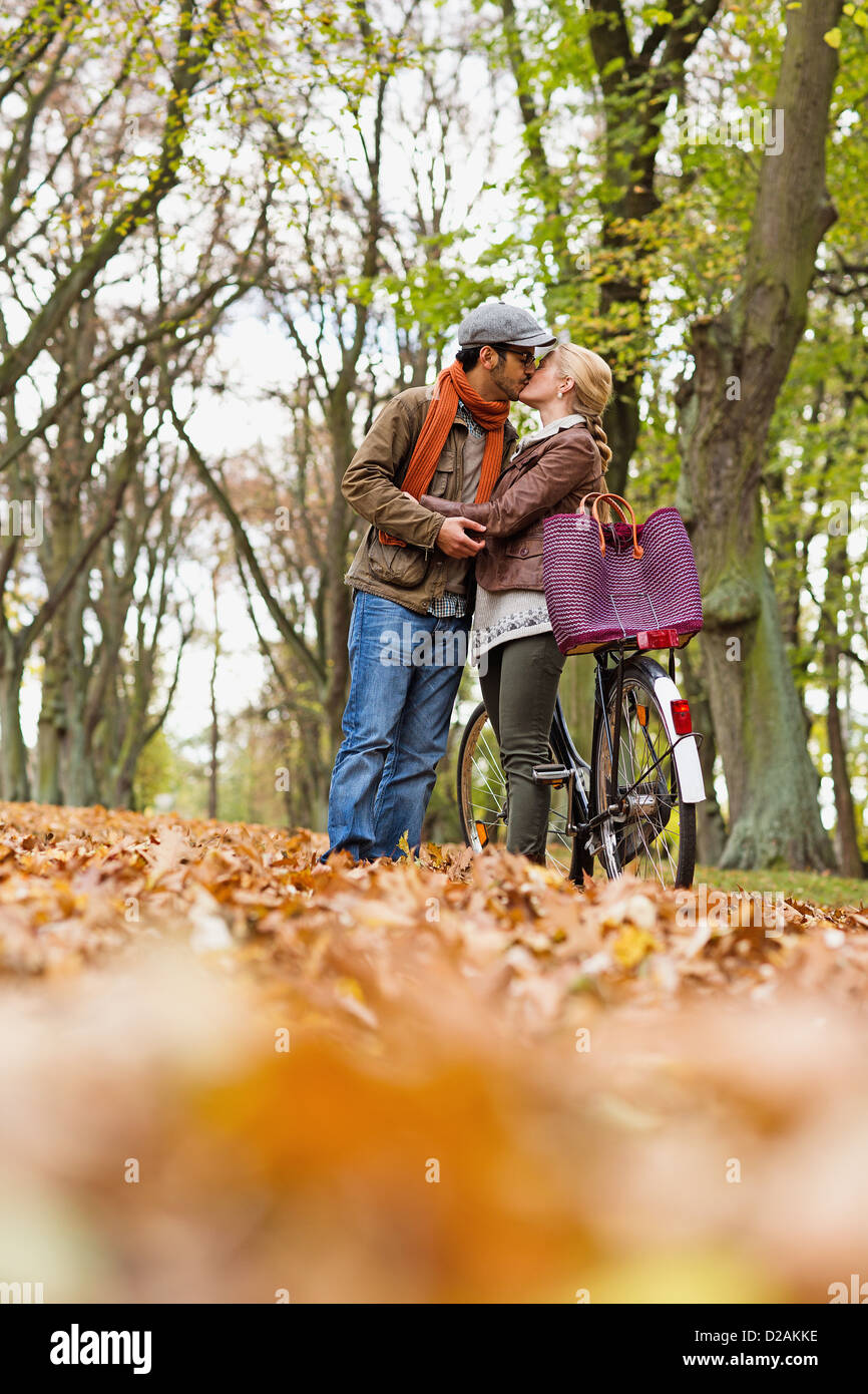 Couple kissing by bicycle in forest - Stock Image