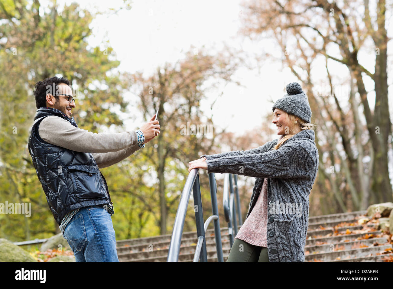 Man taking picture of girlfriend in park - Stock Image