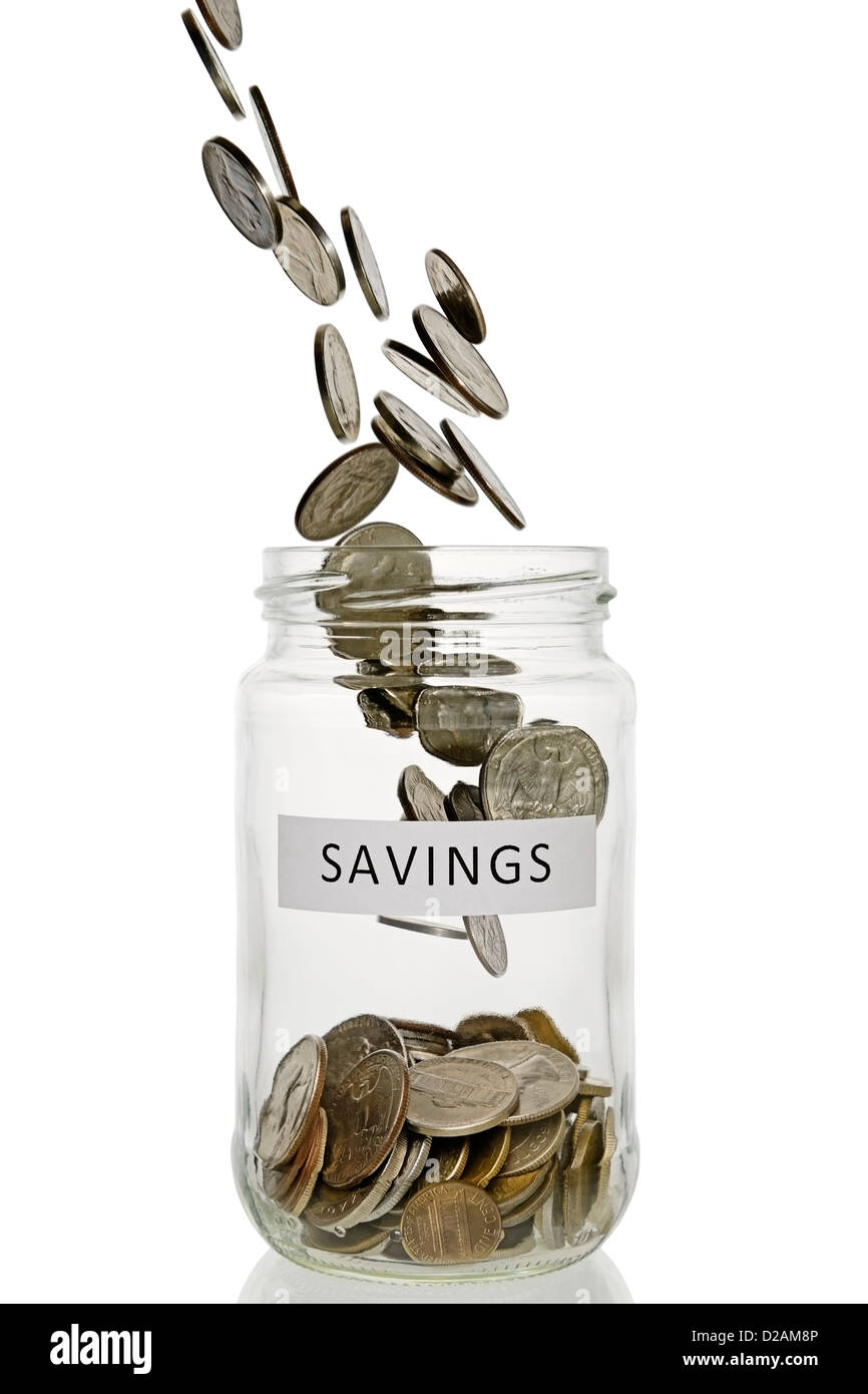 Savings Jar With Coins Pouring Into It, US Currency. - Stock Image