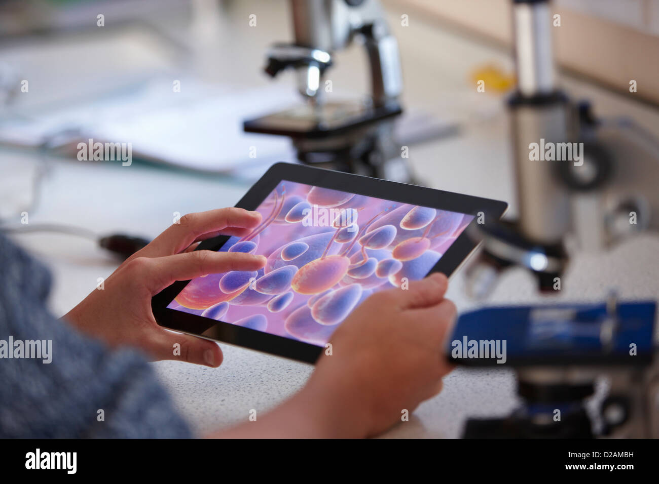Student using tablet computer in class - Stock Image