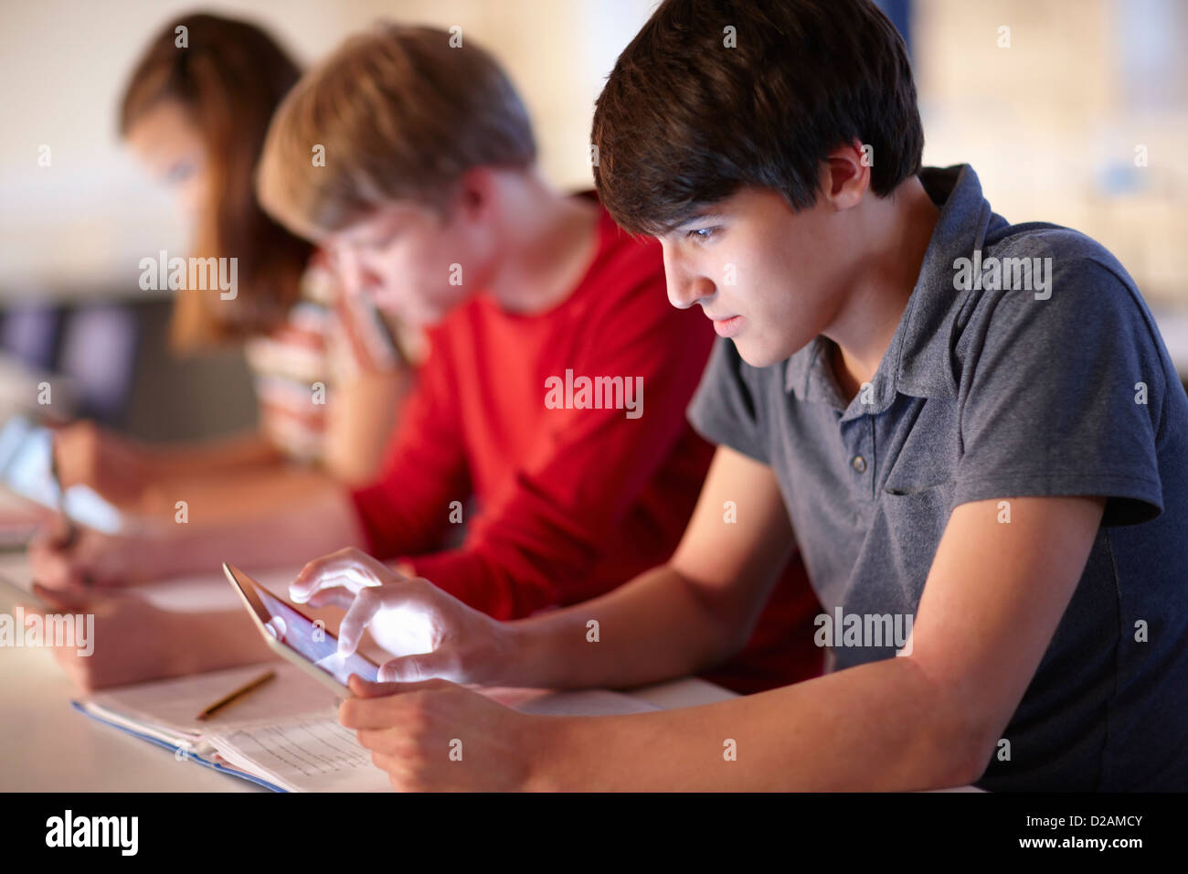 Students using tablet computers in class - Stock Image