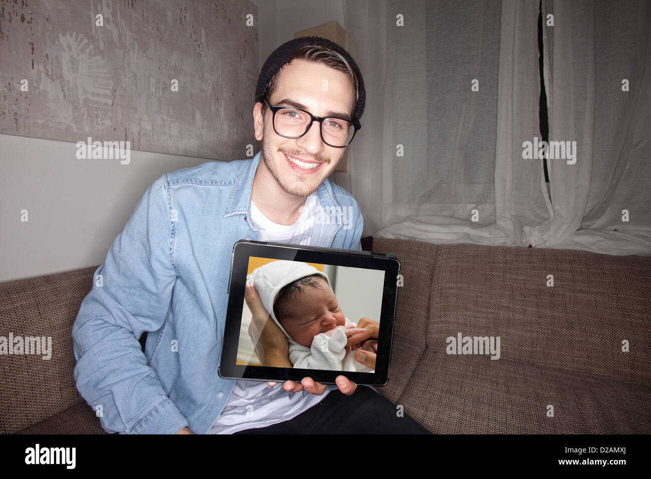 Man with newborn on tablet computer Stock Photo