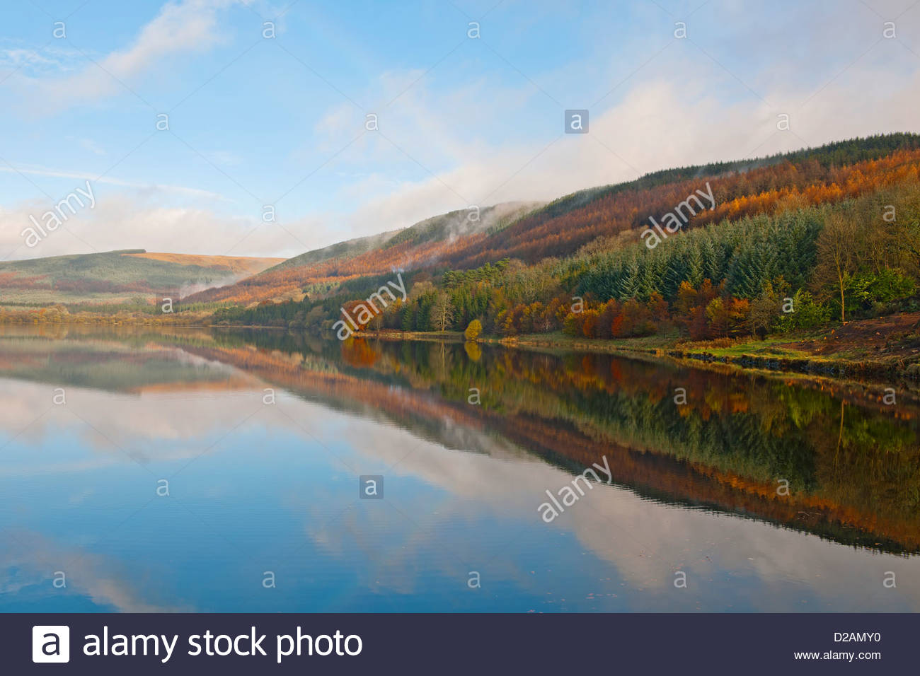 Rural hills reflected in still lake Stock Photo