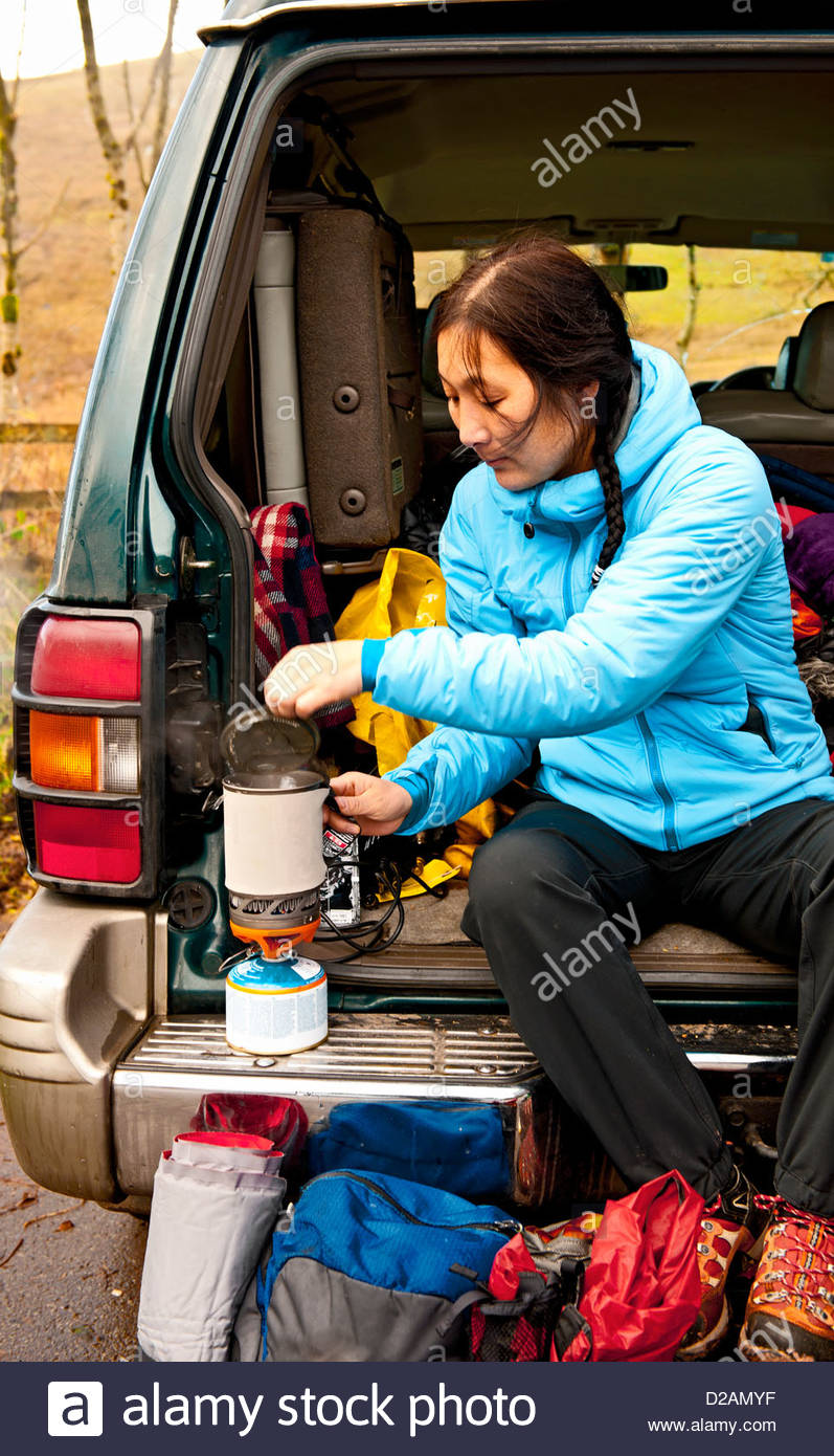 Hiker making tea in car trunk - Stock Image