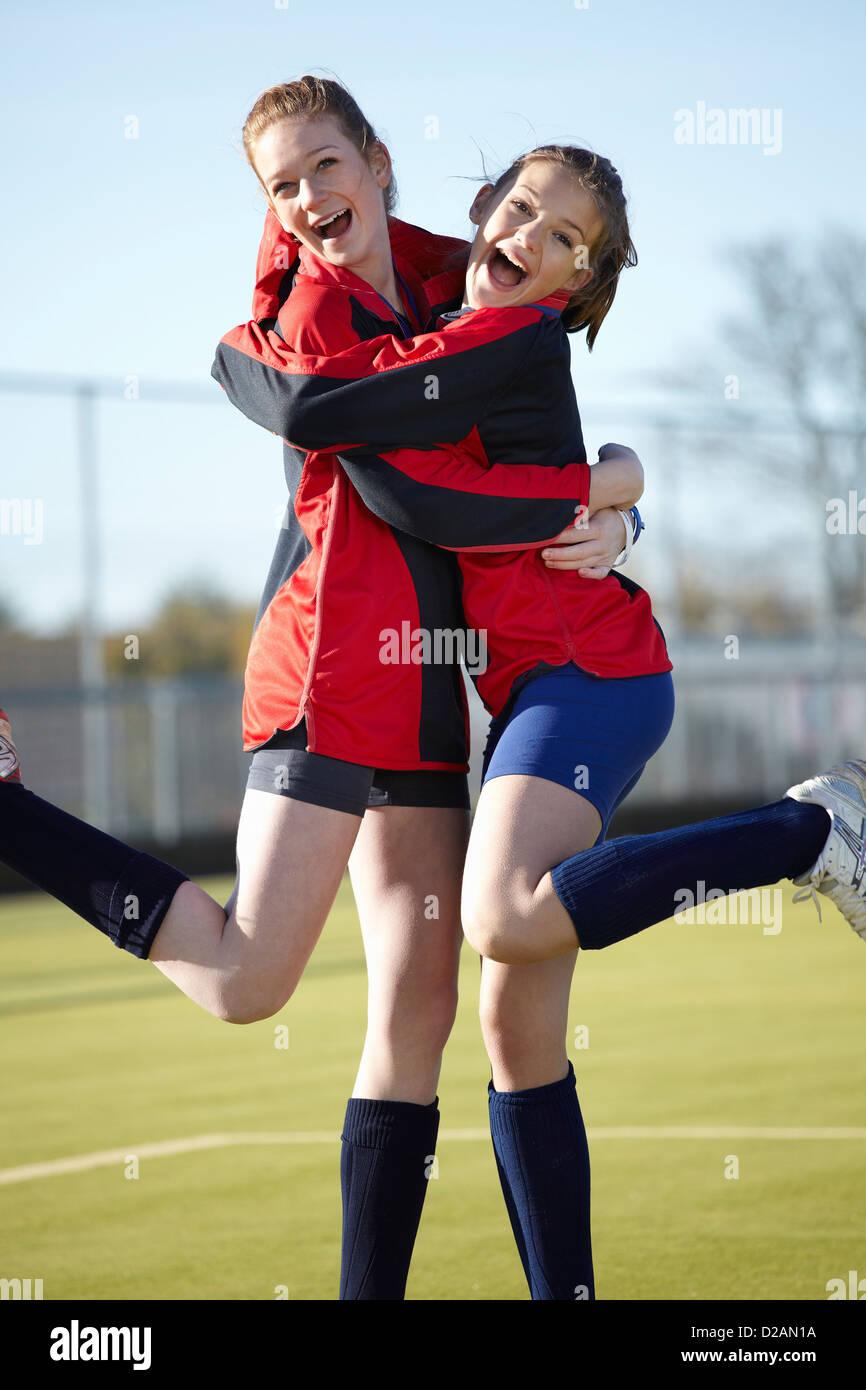 Team members hugging on field - Stock Image