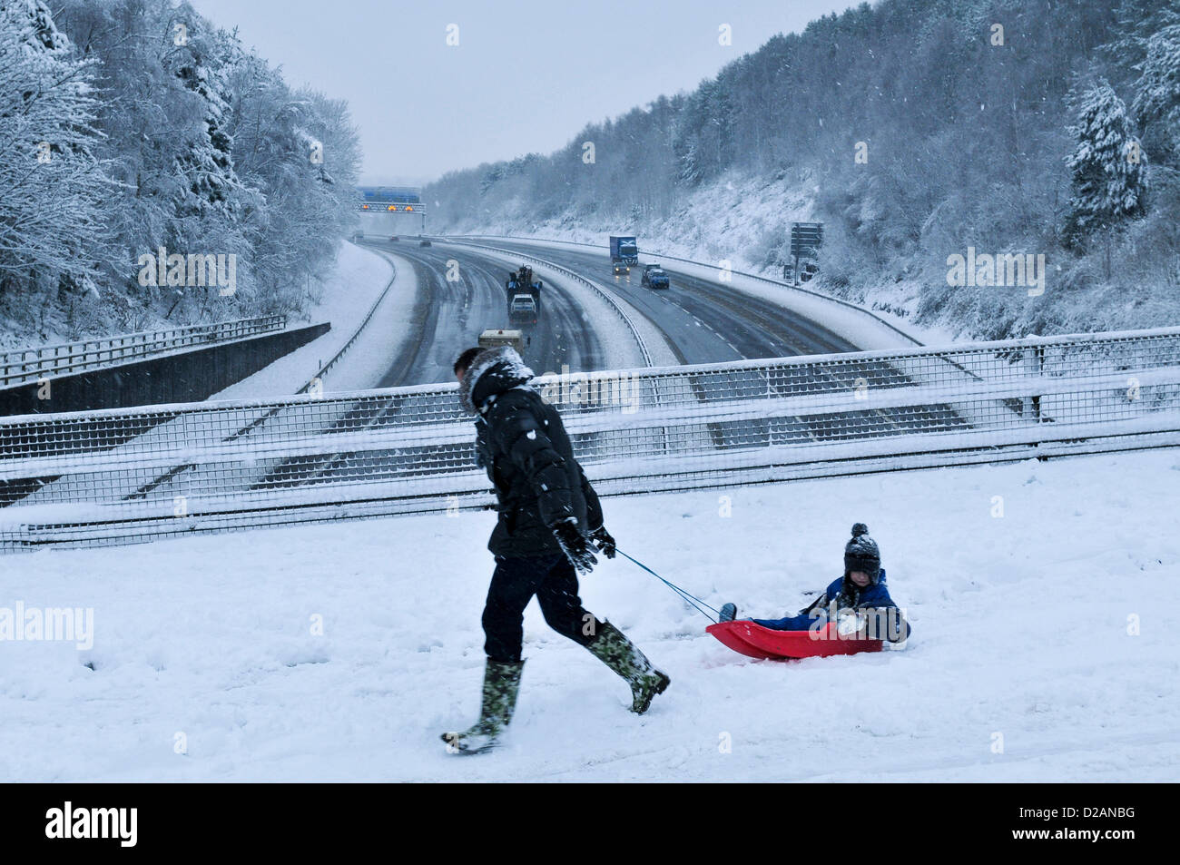 M4 Motorway. Cardiff, UK. Friday 18th January 2013. A man pulls his child on a sledge across a bridge over the M4 - Stock Image